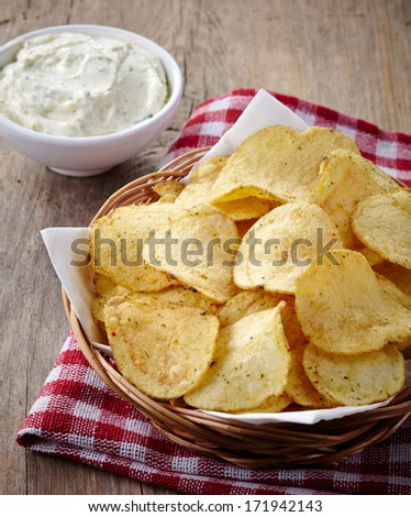 Basket of potato chips and bowl of dip on wooden background - stock photo