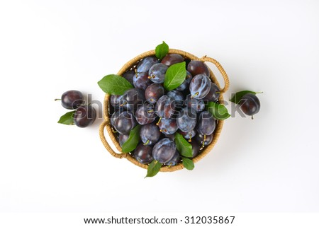 basket of ripe plums on white background - stock photo
