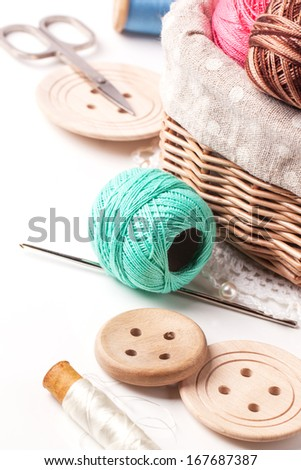 Basket of threads with wooden buttons and scissors over white - stock photo