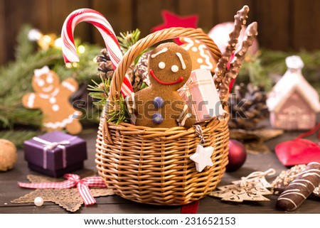Basket of various Christmas treats, gingerbread man, gifts and decorations on the table - stock photo
