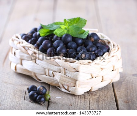 Basket with black currant on a wooden background - stock photo