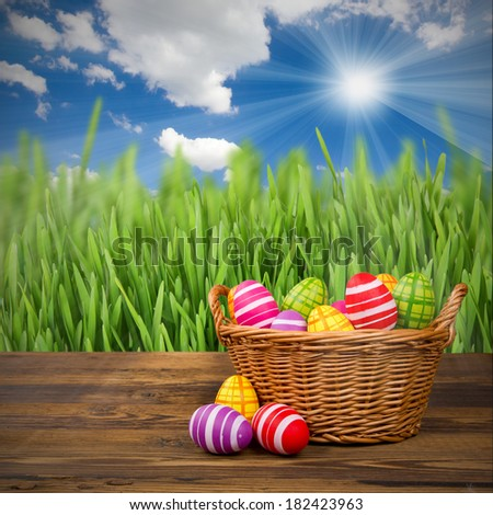 Basket with easter eggs on wooden desk - stock photo