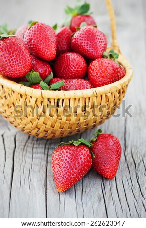 Basket with fresh and ripe strawberries on old wooden background - stock photo