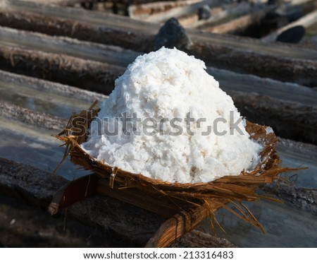 Basket with fresh extracted sea salt on wooden tanks for water evaporation. It is a unique tradition of production dating back over 900 years in Bali, Indonesia. - stock photo