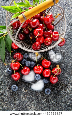 basket with fresh juicy Berries and ice cubes in the shape of heart . summer morning . healthy breakfast. close-up - stock photo