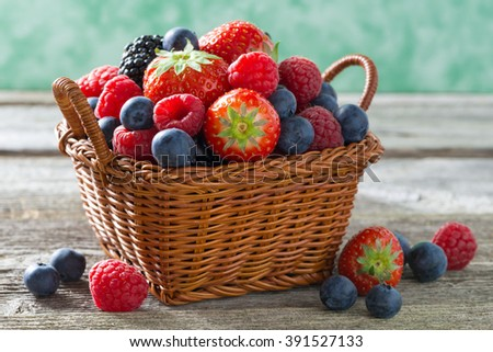 basket with fresh juicy berries on a wooden table, close-up, horizontal - stock photo