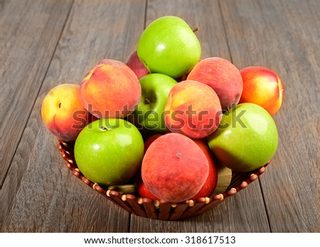 Basket with fruits apples peaches nectarines - stock photo