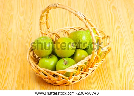 basket with green apples on a kitchen table - stock photo