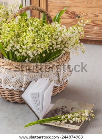 Basket with lilies of the valley (Convallaria majalis) next to notebook with old photographs on the window - stock photo
