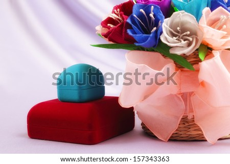 Basket with paper flowers and velvet boxes - stock photo