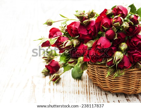 Basket  with red roses on a wooden  background - stock photo