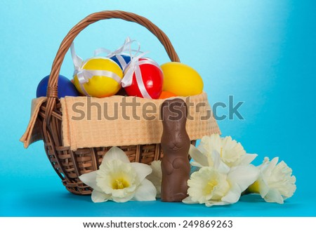 Basket with the eggs decorated with ribbons, flowers and a chocolate rabbit on a blue background - stock photo