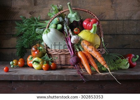 Basket with vegetables: vegetable marrow, pumpkin, eggplant, pepper, carrots, cucumbers and tomatoes. Vegetables in a basket. - stock photo