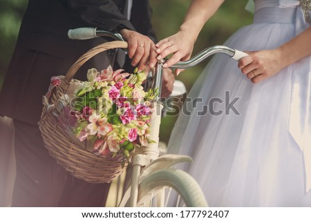 Basket with wedding flowers on the handlebars bride and groom with white bicycle  - stock photo