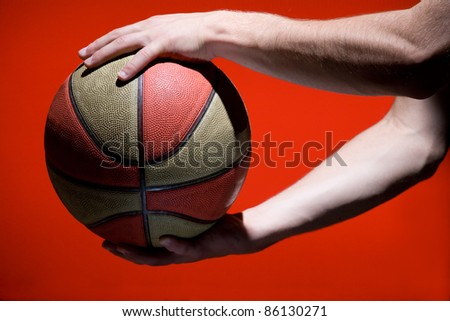 Basketball ball in hands isolated on red background - stock photo