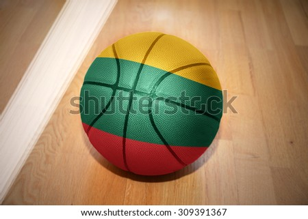 basketball ball with the national flag of lithuania lying on the floor near the white line - stock photo