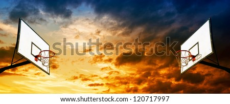 Basketball board with hoop and cage against the dusk sky, abstract sports background. - stock photo