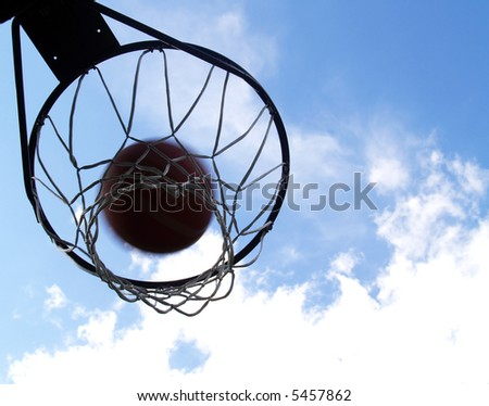 basketball going through an outdoor basketball hoop - stock photo