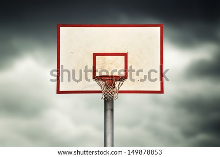 Basketball hoop and cage against dark sky - stock photo