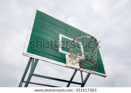 Basketball Hoop  - Outdoor basketball hoop and green backboard, taken from a Bottom side view. Isolated on sky background. - stock photo