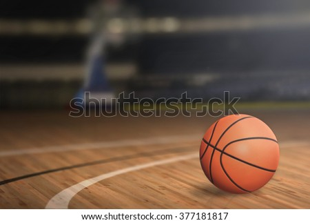 Basketball on Court Floor close up with blurred arena in background - stock photo