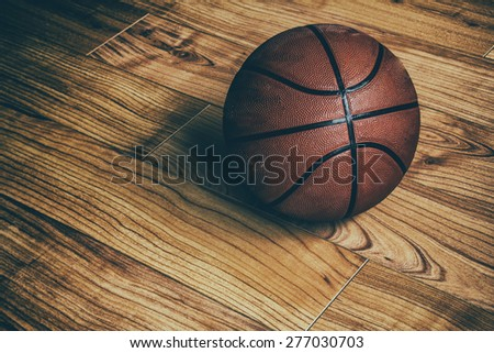 Basketball on Hardwood 1. A basketball laying on the ground of a hardwood court in a gymnasium. - stock photo