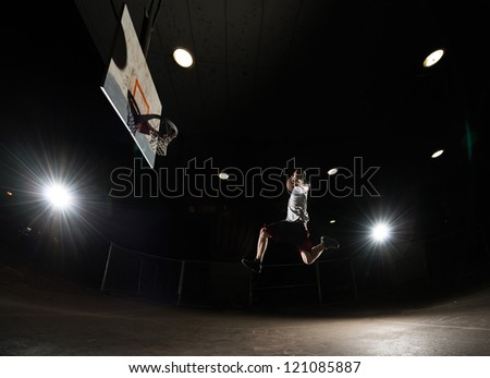 Basketball player at night jumping and aiming at hoop with lights on - stock photo