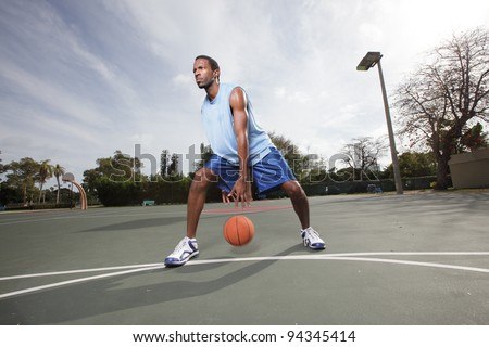 Basketball player dribbling the ball between his legs - stock photo
