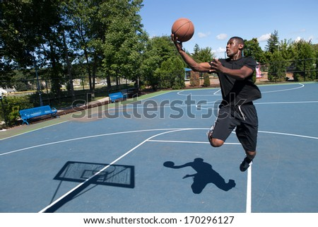 Basketball player driving to the hoop for a layup. Shallow depth of field. Contrasty shadow silhouette of backboard and player clearly visible. - stock photo