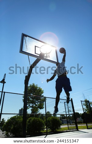 Basketball player dunk silhouette.  Intentionally back lit with bright lens flare coming through the clear backboard. - stock photo