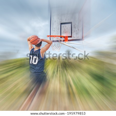 basketball player dunking in a blurred playground - stock photo