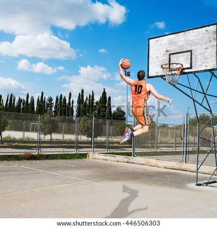 basketball player dunking in a playground - stock photo