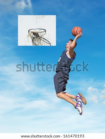 basketball player dunking with the sky in the background - stock photo