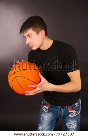 Basketball player holding ball isolated on a black background - stock photo