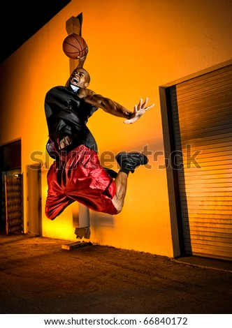 Basketball player jumping with ball in the street. - stock photo