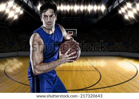Basketball player on a  blue uniform, on a basketball court. - stock photo