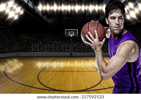 Basketball player on a  purple uniform, on a basketball court. - stock photo