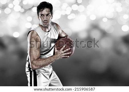 Basketball player on a  white uniform, on a white lights background. - stock photo