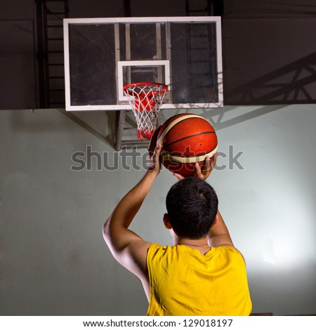 Basketball player prepare to shoot ball in the game - stock photo