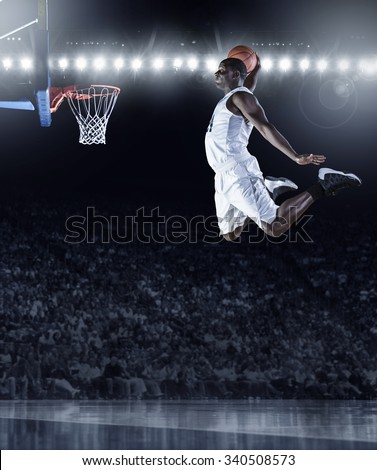 Basketball Player scoring an athletic, amazing slam dunk in a professional basketball game - stock photo