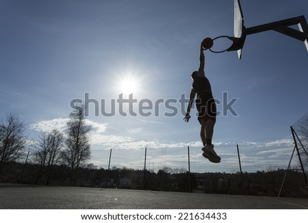 Basketball player silhouette slam dunking on an outdoor court on a sunny day with the sun gleaming in the background - stock photo
