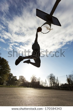 Basketball Player Slam Dunk SIlhouette - stock photo