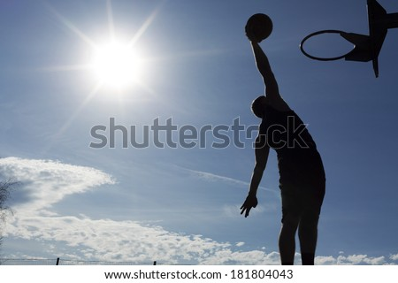 Basketball player slam dunk silhouette with the sun beaming down - stock photo