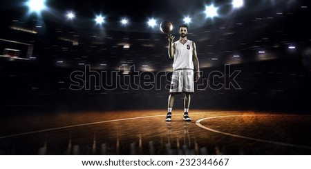 Basketball player spinning ball in gym  panorama view - stock photo