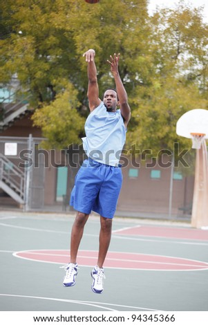 Basketball player throwing the ball - stock photo