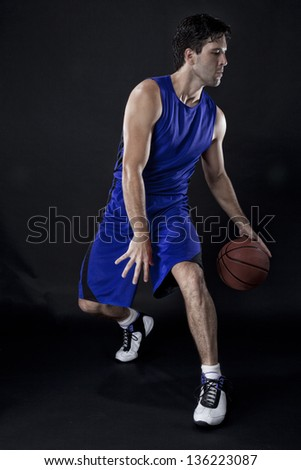Basketball player with a ball in his hands and a Blue uniform. photography studio. - stock photo