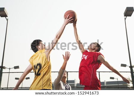 Basketball players fighting for a ball - stock photo
