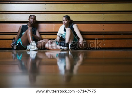 Basketball players resting on the sidelines - stock photo