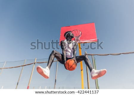 Basketball street player making a rear slam dunk - Sporty black man playing basketball outdoor - stock photo