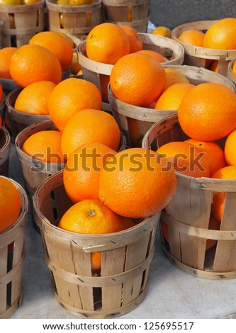 Baskets full of beautiful oranges for sale at the farmer's market on a bright, sunny morning. - stock photo